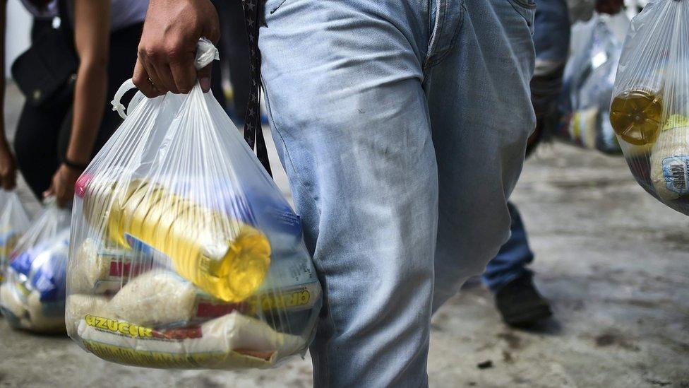 Pessoa leva sacola de comida