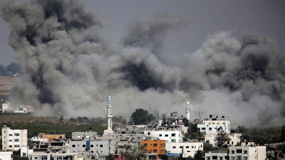 Smoke plumes rising after an Israeli airstrike hit Gaza City, northern Gaza Strip, Thursday, July 31, 2014