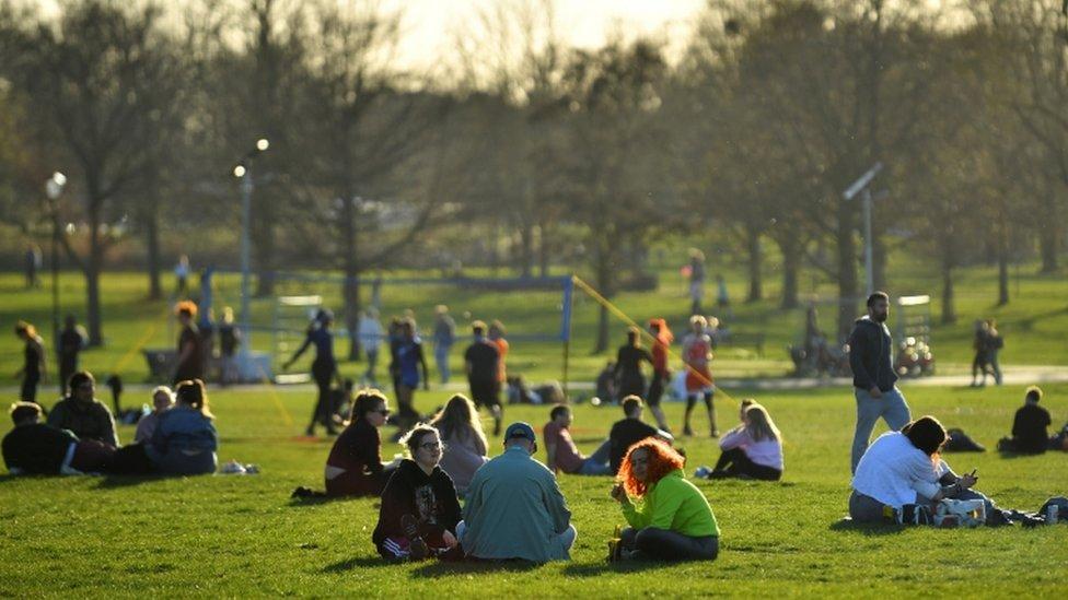 Grupo de personas se reúnen en un parque de Londres.
