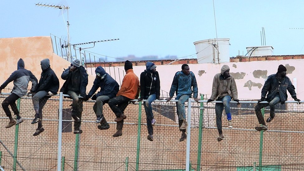Migrants sit atop a border fence separating Morocco from Spanish enclave of Melilla, 19 Feb 15