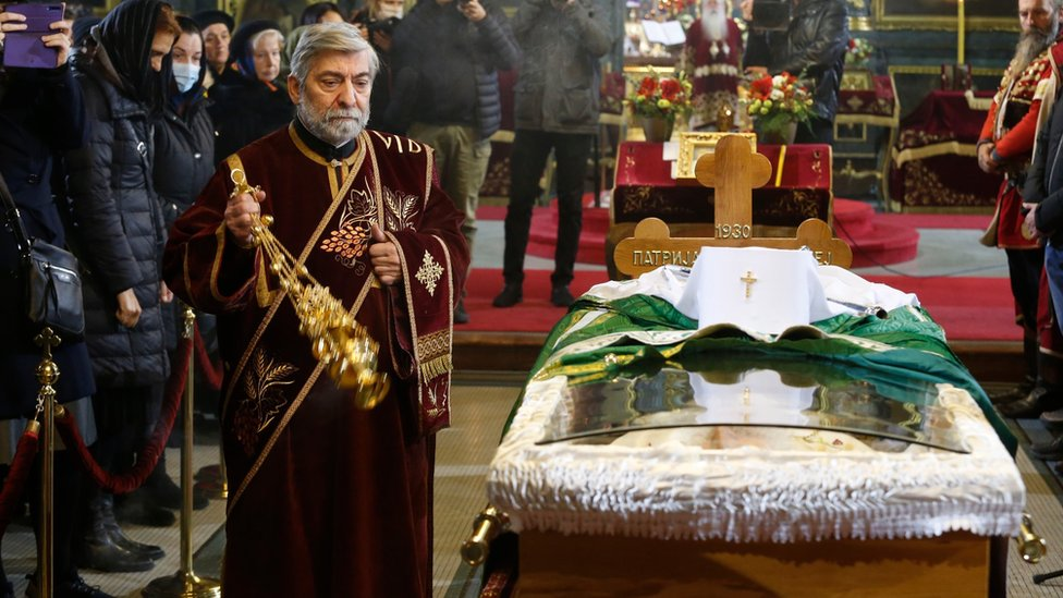 A priest delivers a service to the late Serbian Patriarch Irinej in Belgrade, Serbia, 21 November 2020.
