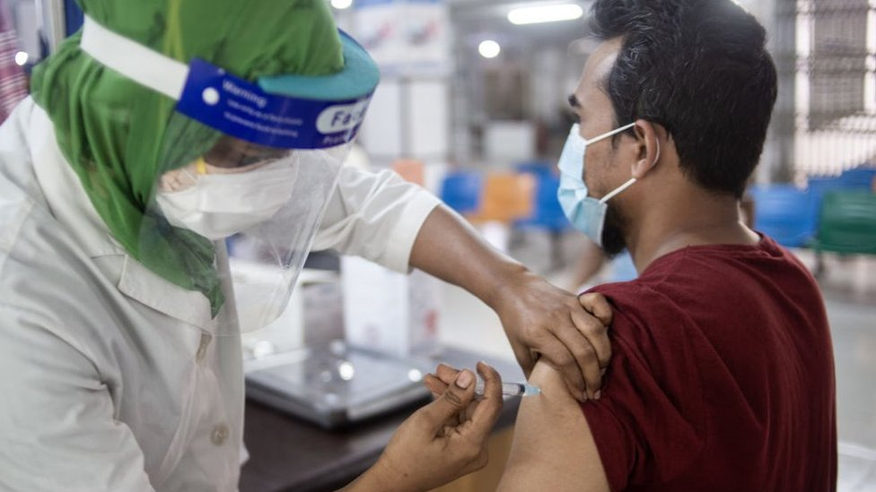 A man is vaccinated by a woman with a face shield in Bangladesh