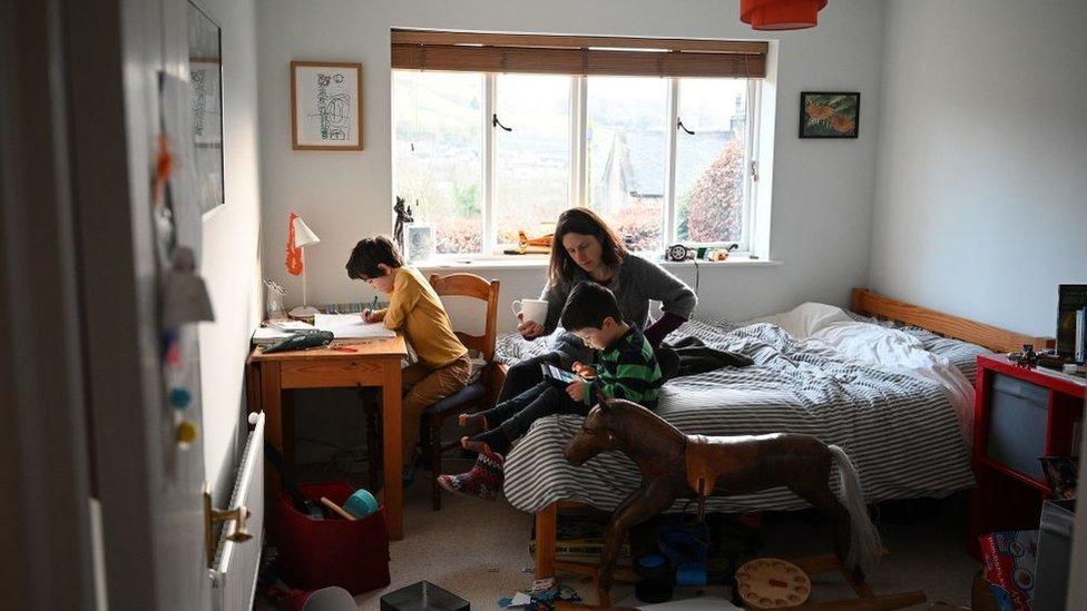 Una madre con dos hijos dentro de una habitación