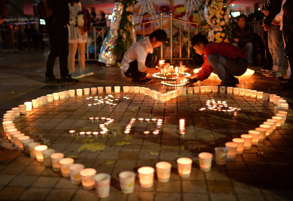 This picture taken on 2 March 2014 shows Chinese mourners lighting candles at the scene of the terror attack at the main train station in Kunming, southwest China's Yunnan Province.