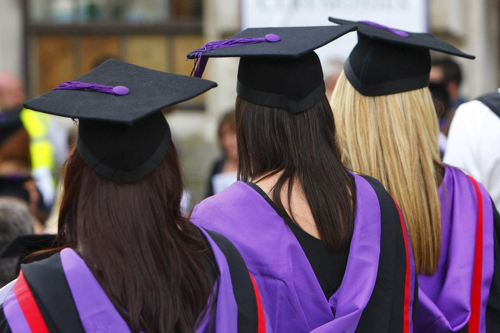 Three university graduates in mortar boards and purple gowns
