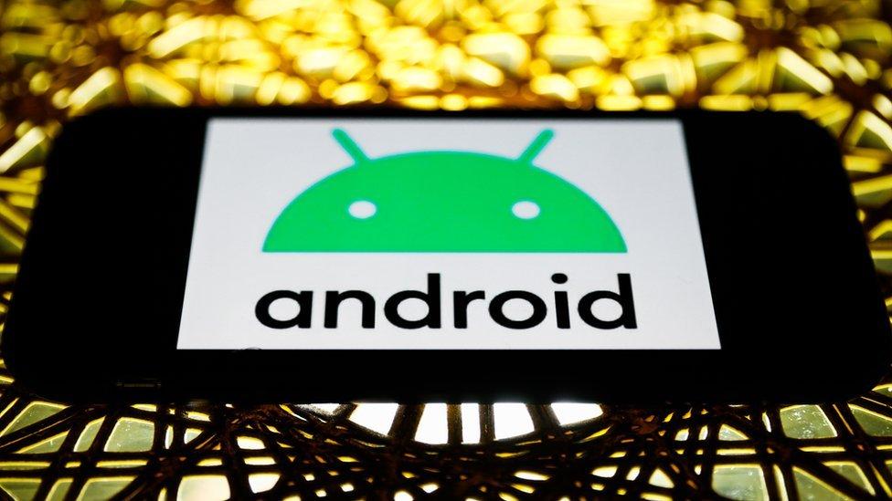 شعار أندرويد على شاشة الهاتف في الوضع الأفقي، موضوع على طاولة مضاءة بضوء ذهبي