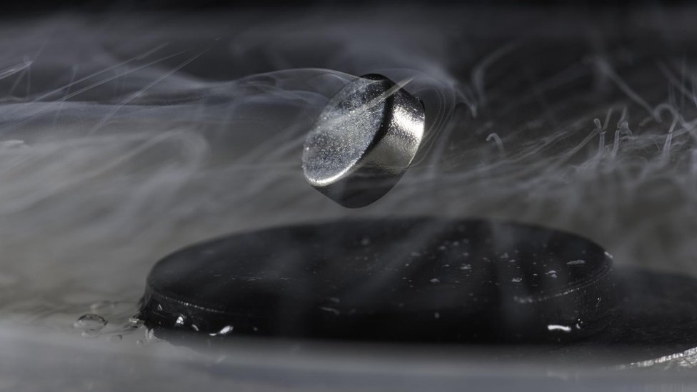 A magnet floats above a superconductor cooled with liquid nitrogen