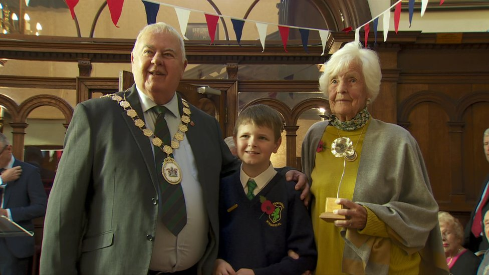 Maureen Lightbody, holding her silver poppy, with Mayor Bill Keery and a schoolboy from Bangor