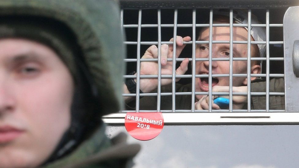 A protester shouts from a police bus after detention on Sunday in Moscow