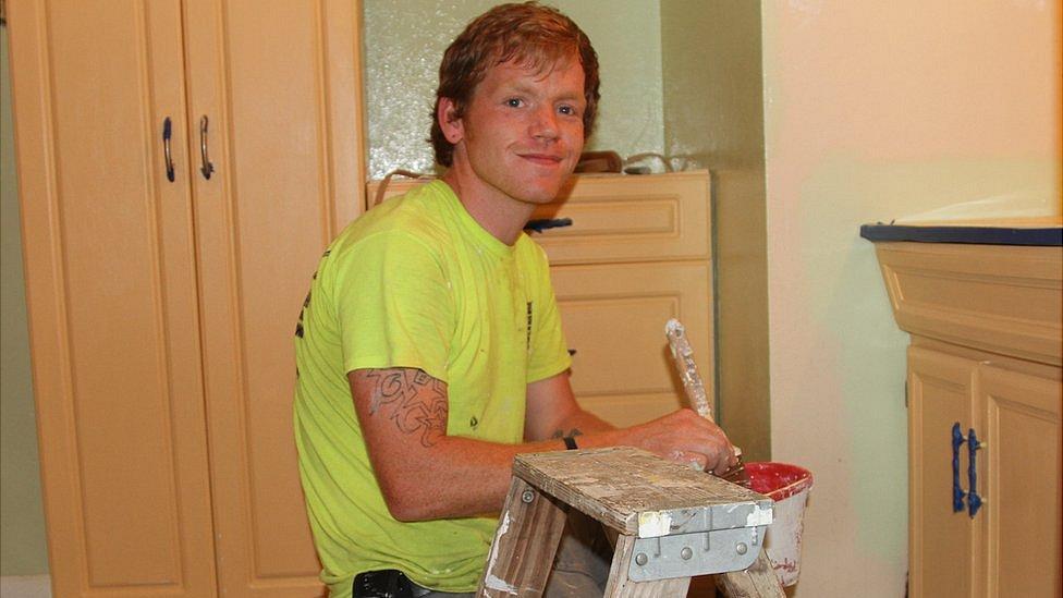 Sam Duval painting a bathroom wall
