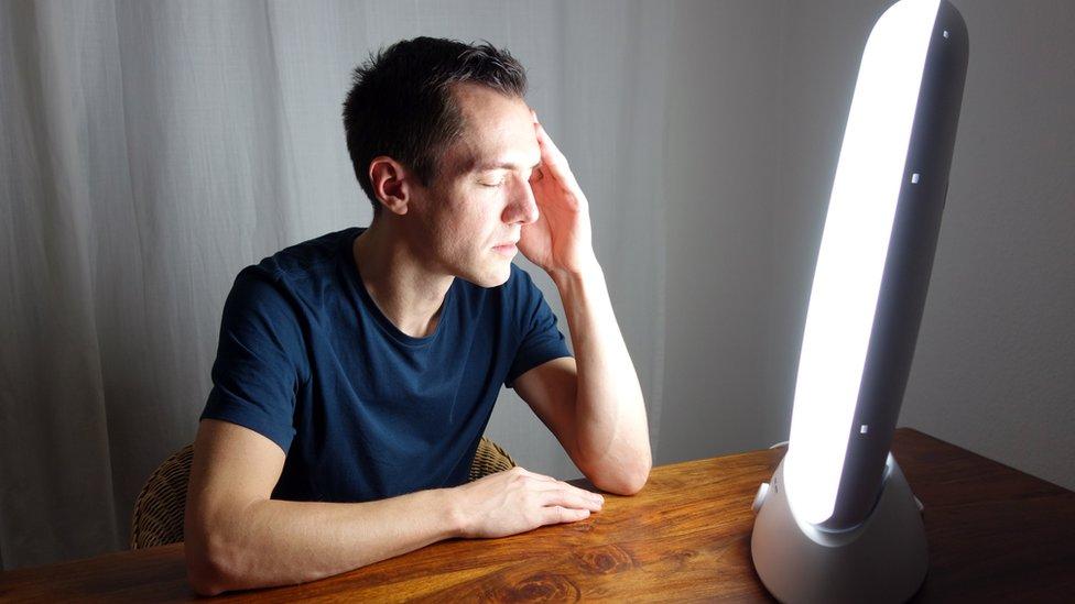 Homem em frente a uma caixa de luz