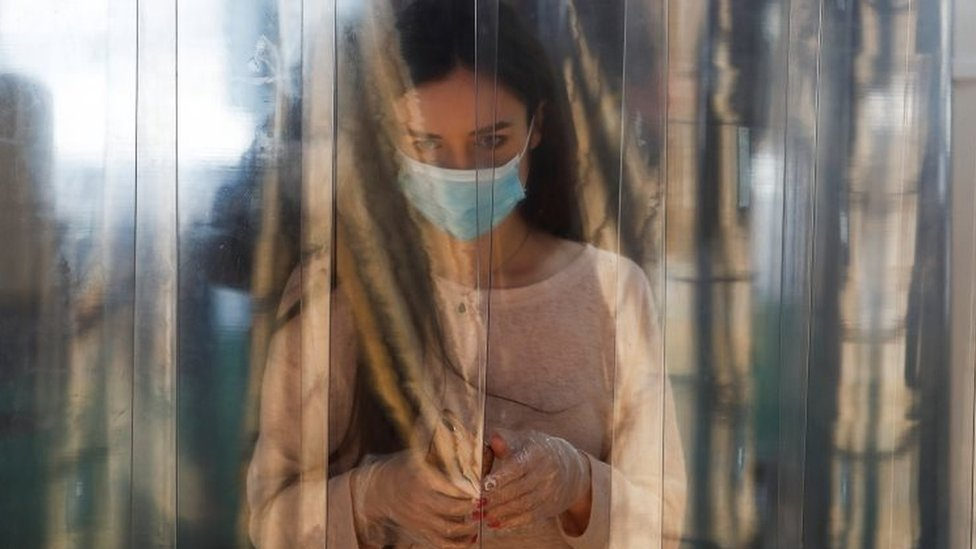 Seorang perempuan mengenakan masker dan sarung tangan berjalan melalui bilik disinfektan.
