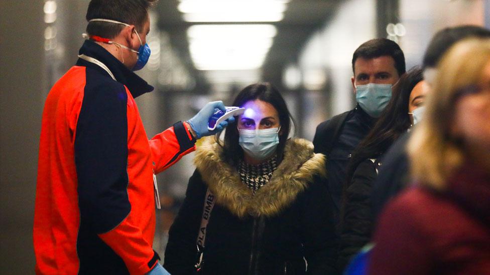 A los pasajeros provenientes de Milán, Italia, se les verifica la temperatura en el aeropuerto de Cracovia en Balice, Polonia.