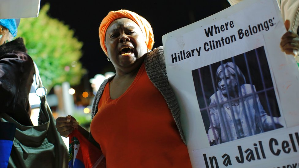 A Haitian woman holds a banner outside Hofstra University before the first presidential debate at the Hofstra University, in Hempstead, New York, on 26 September 2016