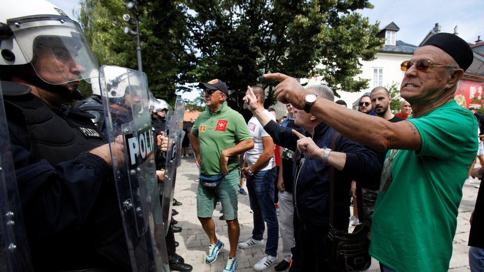 Demonstrators shout at riot police during a protest against enthronement of Bishop Joanikije in Cetinje