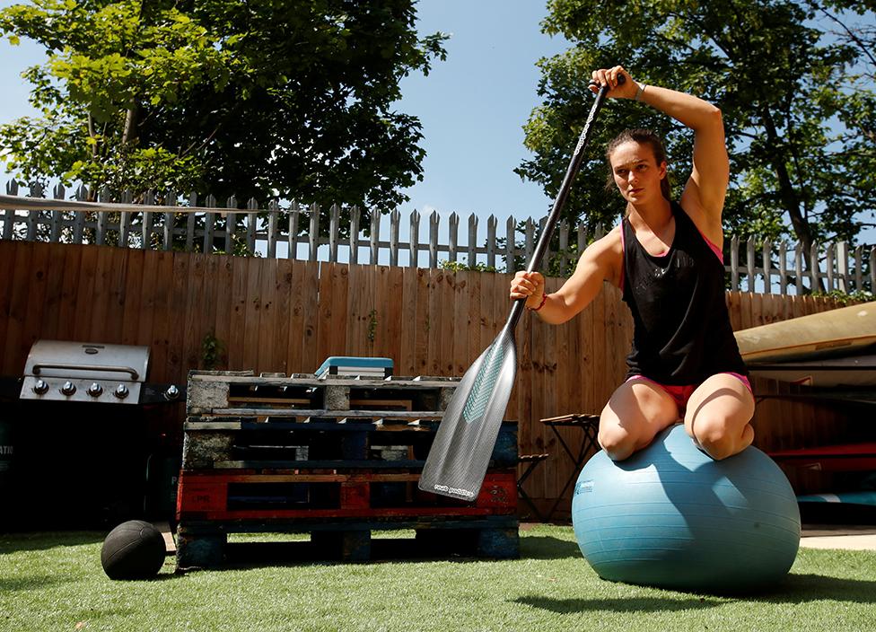 رياضية تحاول الاتزان على كرة بيلاتيس للتوازن بينما تمارس التجذيف