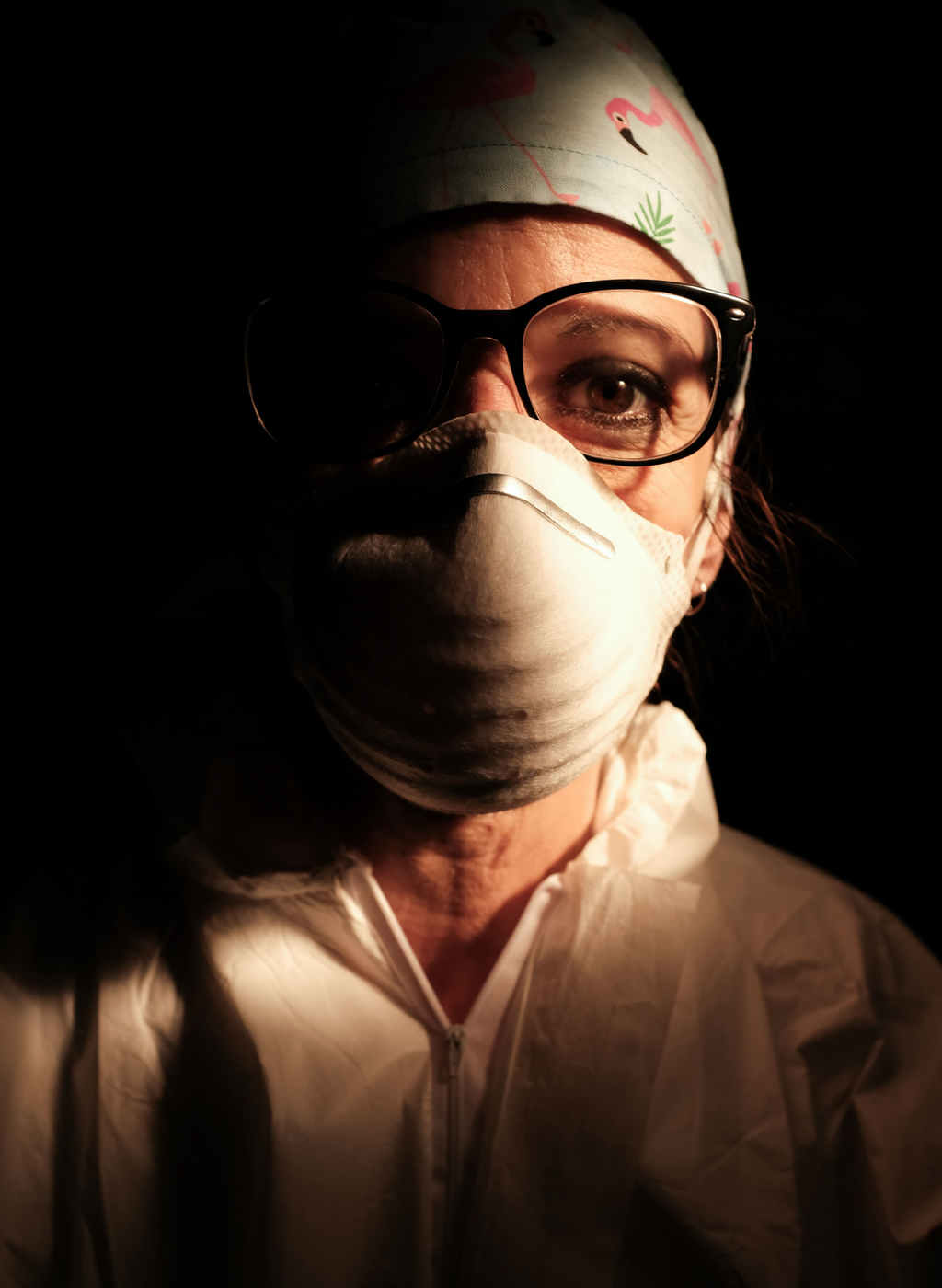 Una enfermera con la cara cubierta con una máscara en un entorno oscuro