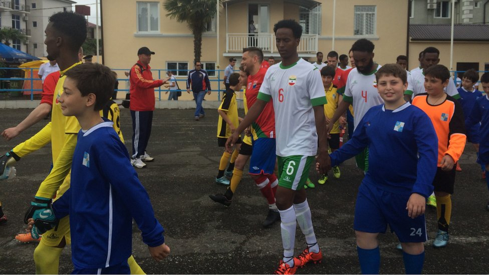 a line of Somaliland footballers being taken on to the pitch by a line of boys