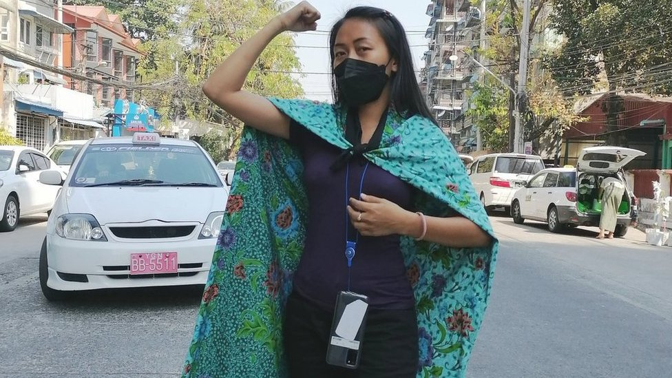 Burmese woman uses her sarong as cape whilst adopting power pose