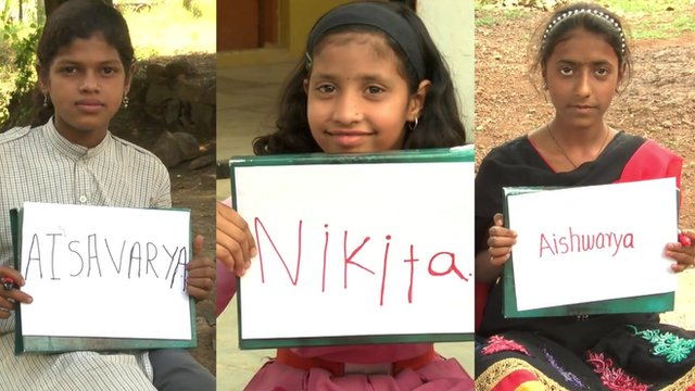 Three girls holding up boards with their new names