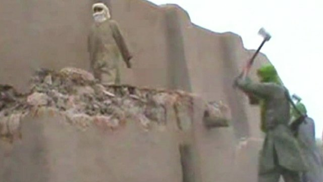 A suspected Islamic militant destroys a historic monument in Timbuktu