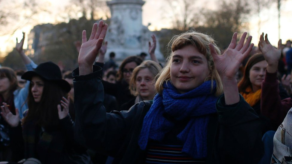 People gesture as they listen to a speech during a gathering by the 'Nuit Debout' movement on Place de la Republique in Paris