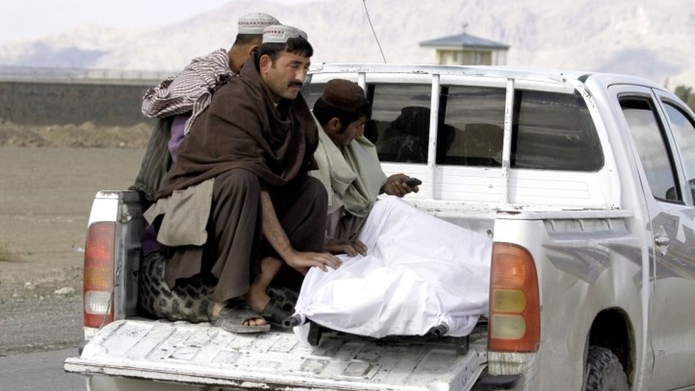 Afghan men move the body of a man after clashes between Taliban fighters and Afghan forces in Kandahar Airfield (09 December 2015)