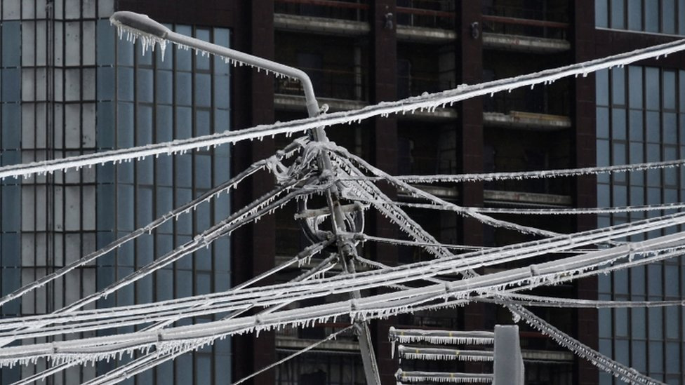 Ice-covered power lines and a light pole are pictured after freezing rain in the far eastern city of Vladivostok, Russia
