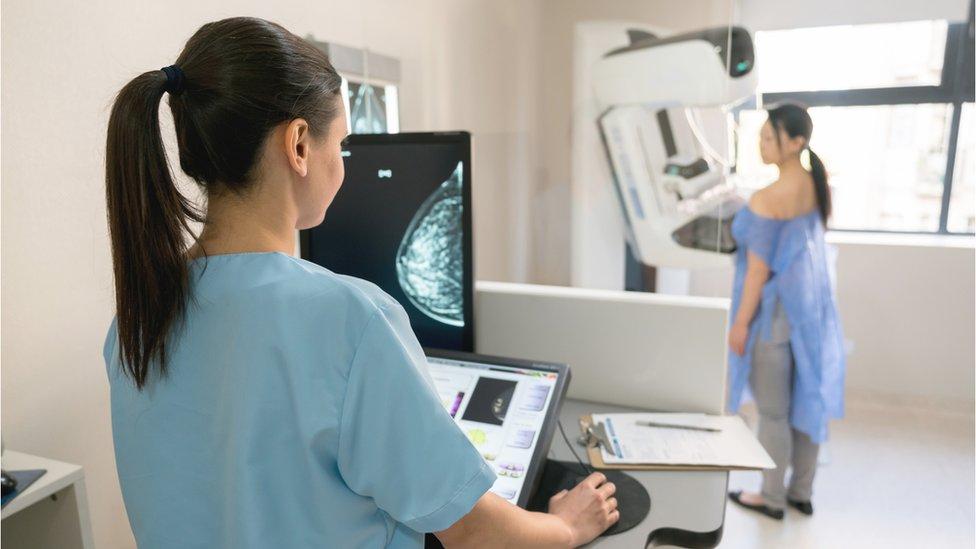 mujer sometiéndose a mamografía