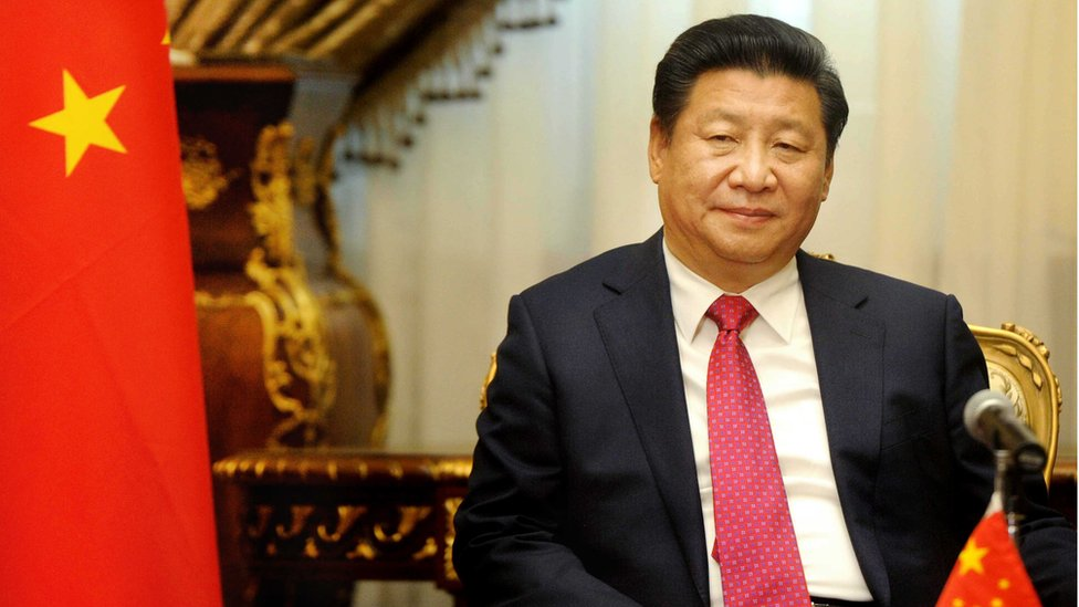 Xi Jinping seated next to a Chinese flag