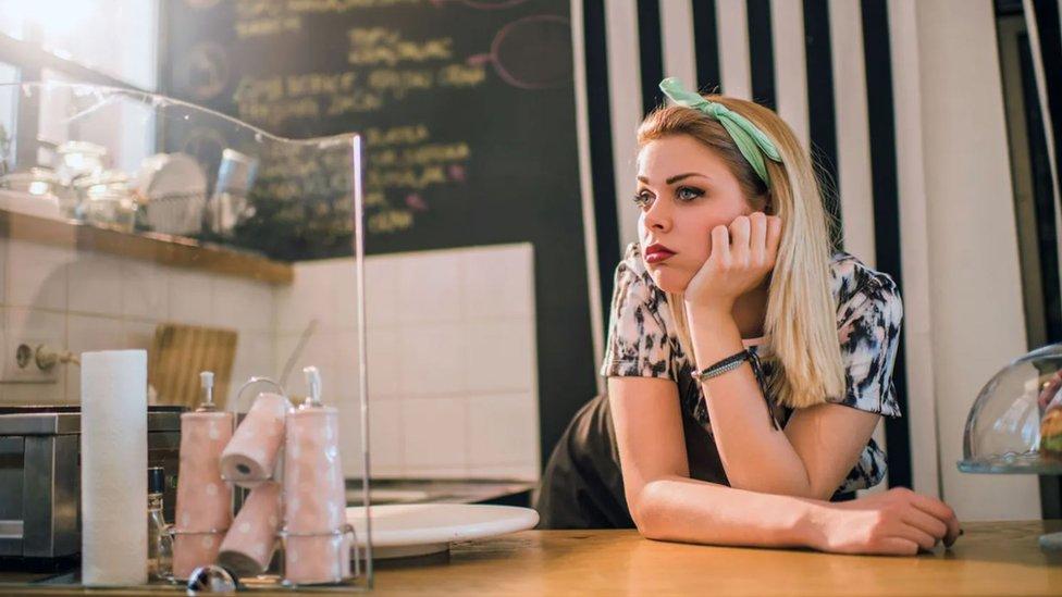 Una mujer con cara de aburrida frente a mostrador.