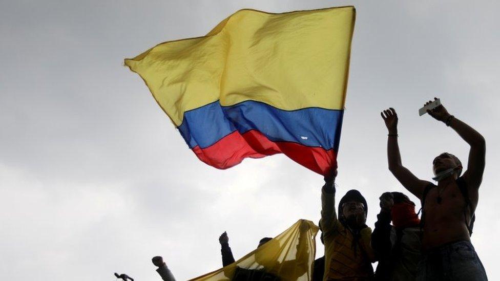Manifestantes con la bandera de Colombia