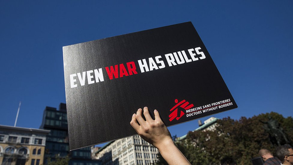 "A placard reading ""Even war has rules"""