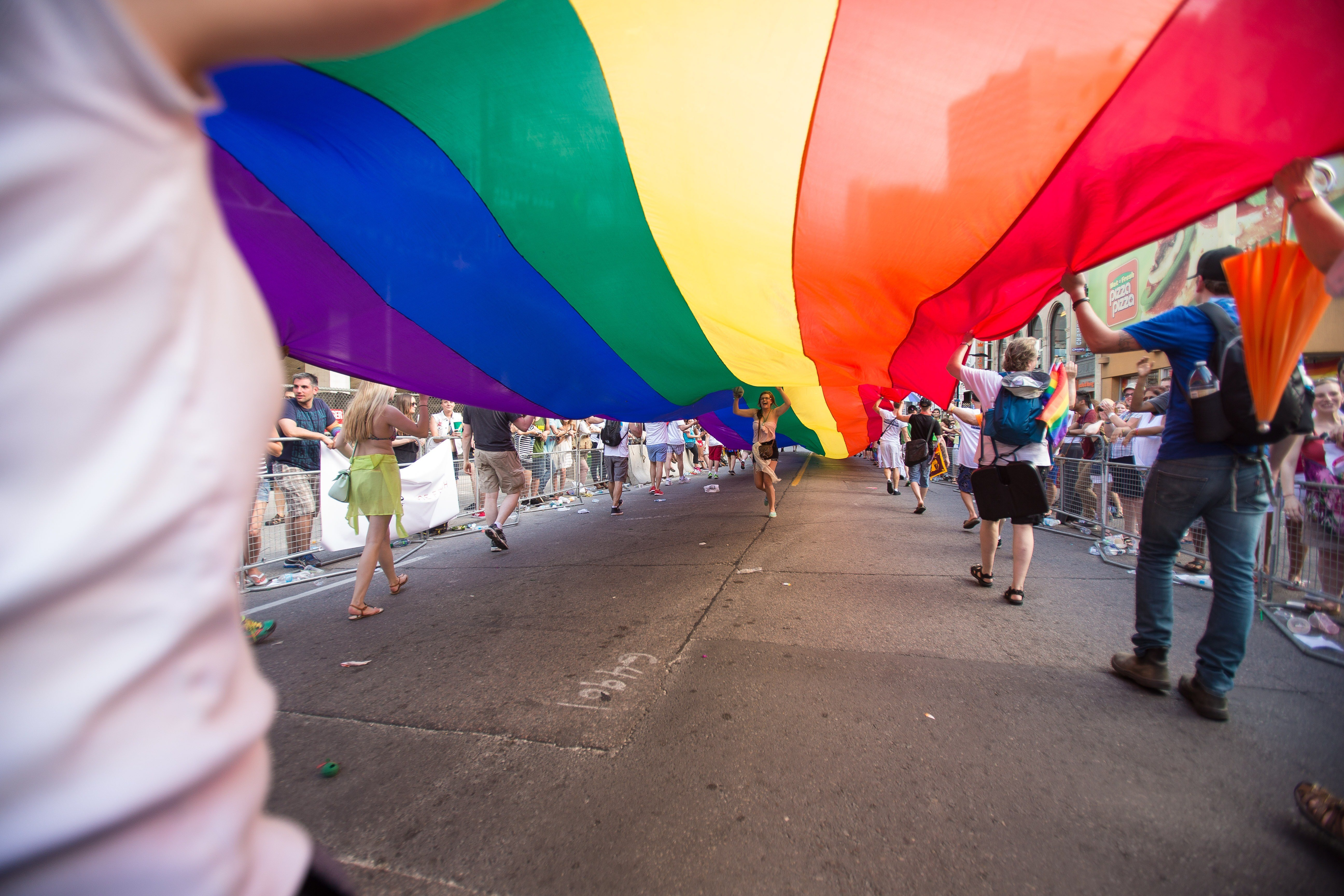 A woman runs under a giant rainbow flag during the WorldPride 2014 Parade in Toronto, Canada,