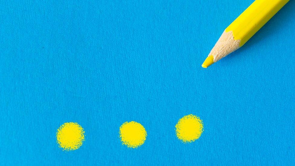 Puntos suspensivos dibujados con un lápiz amarillo en un fondo azul.