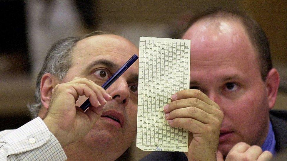 Funcionarios miran las tarjetas de votación en Florida