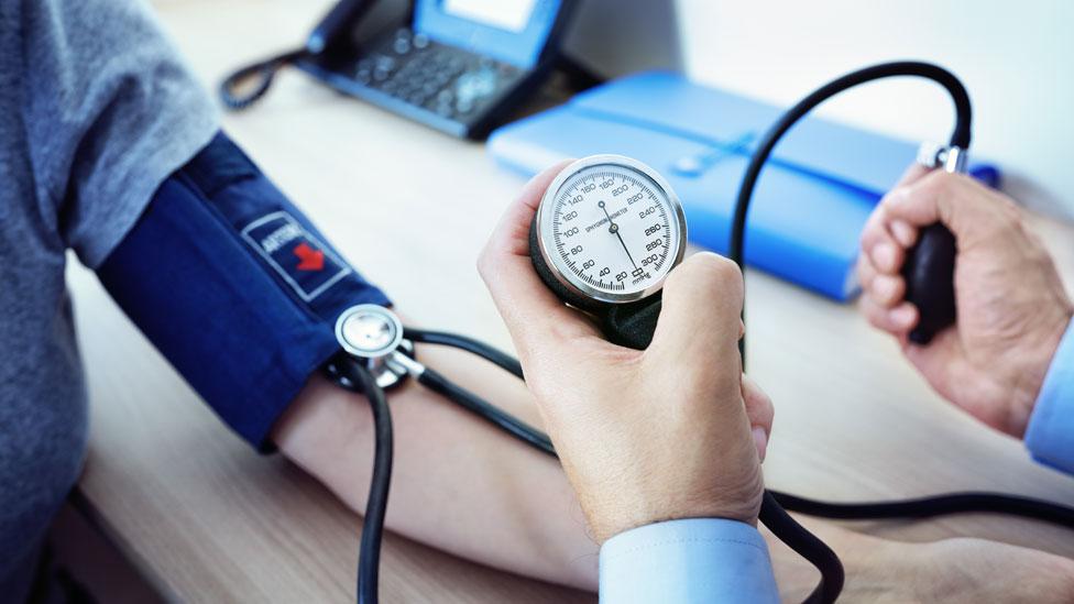 Un médico tomándole la presión a un paciente
