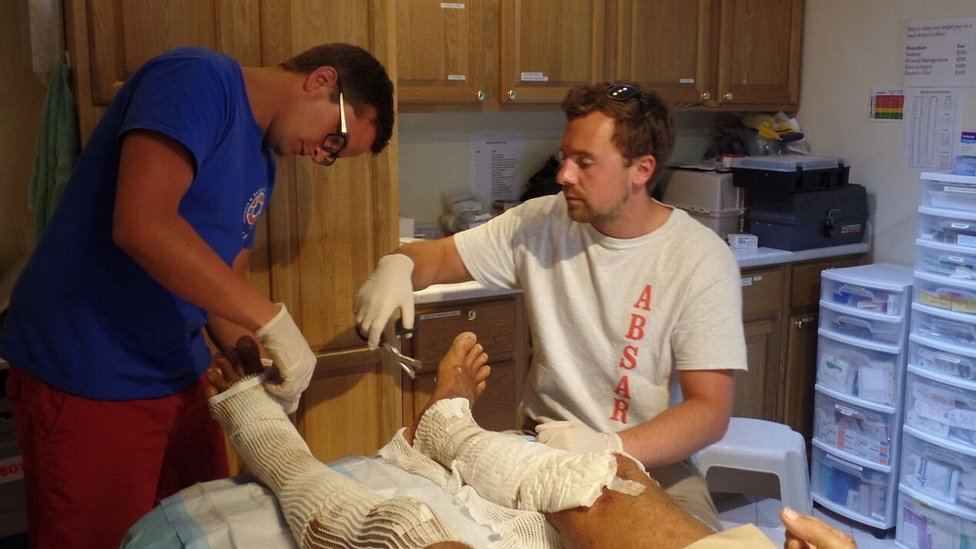 British medical students Tom Nash (left) and Ashley Davies replace a dressing