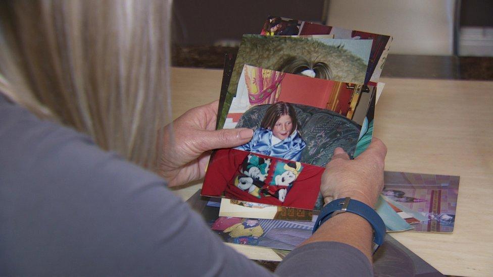 Marie Ferguson looks at photographs of her daughter Raychel