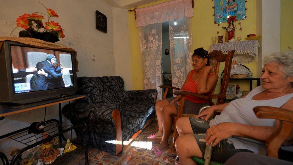 Dos mujeres siguen por televisión la sesión de la Asamblea Nacional cubana desde su casa de La Habana.
