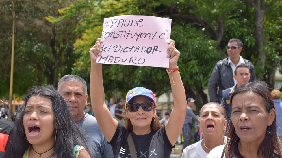 """A woman holds up a sign at an anti-government protest in Merida reading: """"Constituent fraud by dictator Maduro"""""""