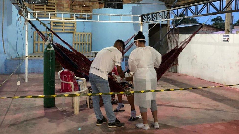 Dois profissionais de jaleco virados em direção a paciente deitado na rede