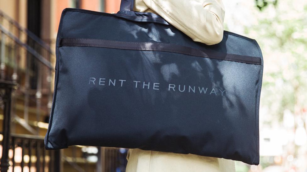 Una mujer lleva una bolsa con el logo de Rent the Runway