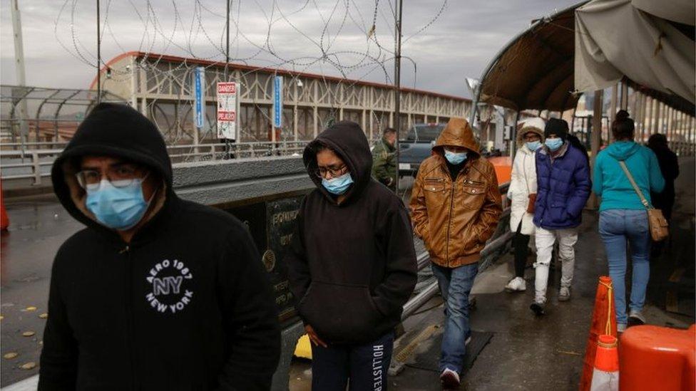 Personas cruzan un puente fronterizo entre México y EE.UU.