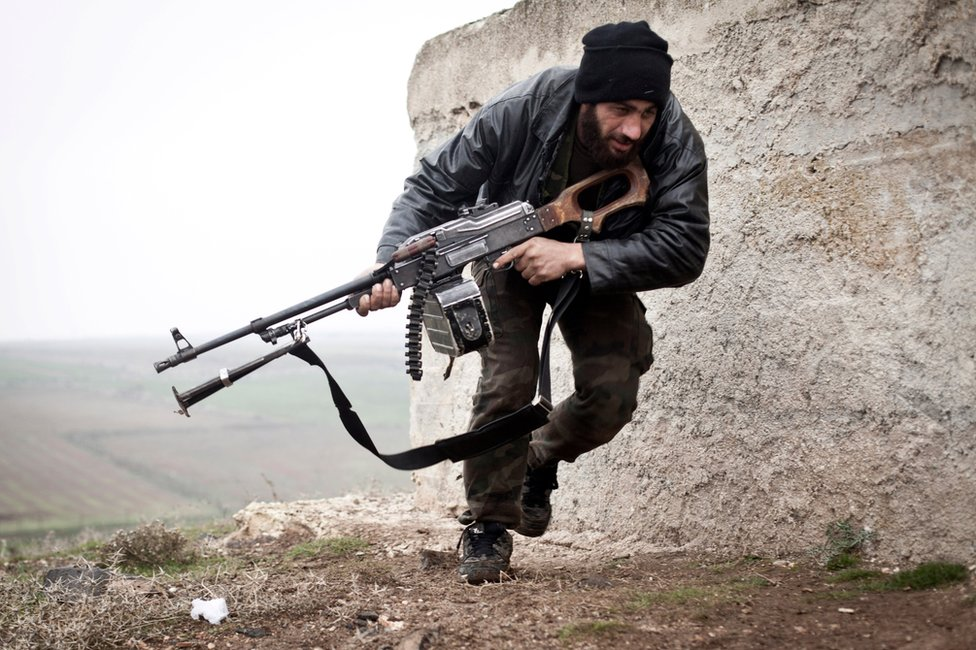 Syrian rebel takes cover during fighting with the Syrian army in Azaz, Syria (17 December 2012)