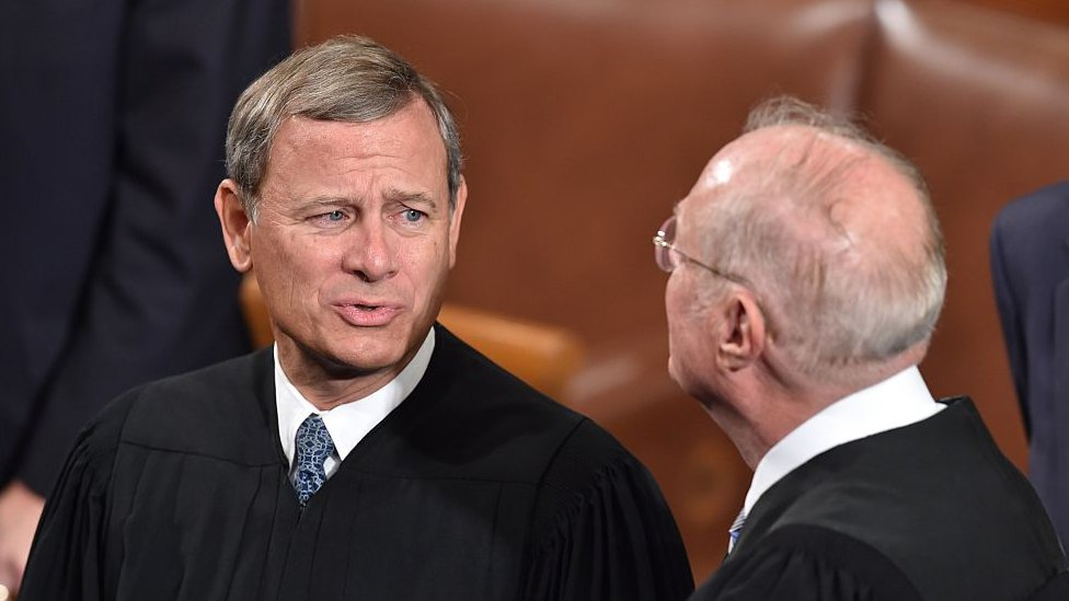 Chief Justice John Roberts talks to Justice Anthony Kennedy.