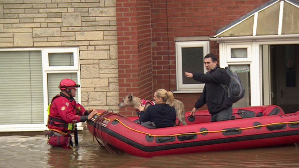 A couple and their dog being rescued in a dinghy boat from their flooded house