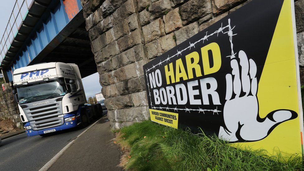 A lorry passing a sign near the Irish border that reads: no hard border