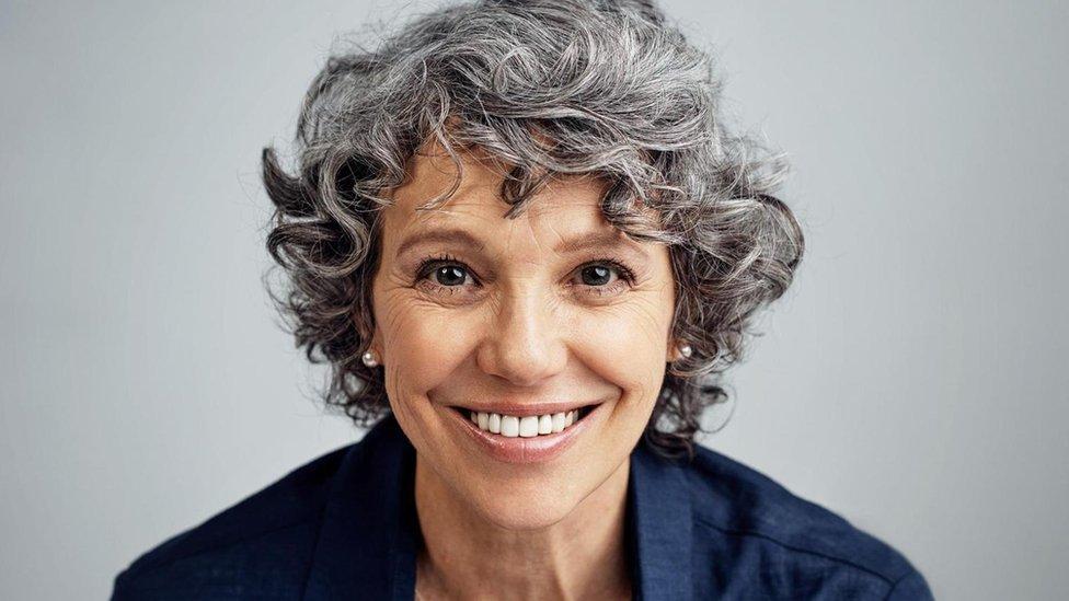 Mujer madura con rulos canosos y sonriendo.