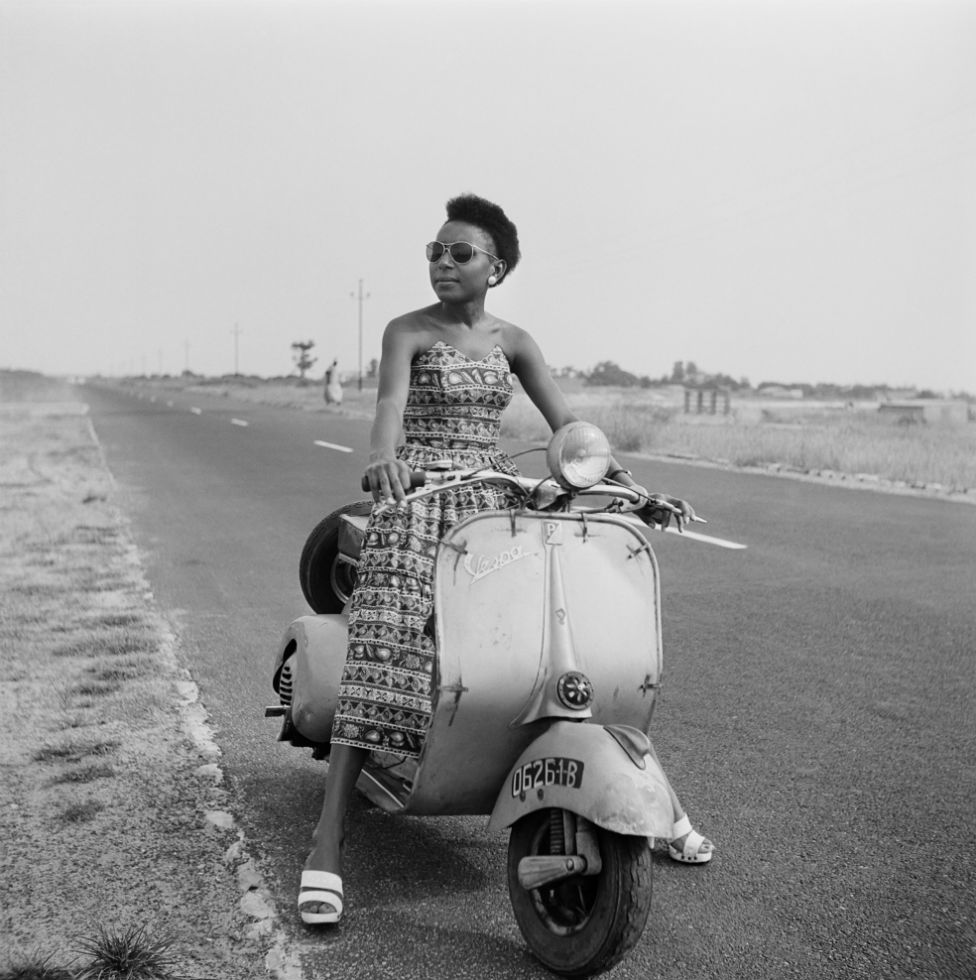 A woman sitting on a moped by the roadside poses for the camera.